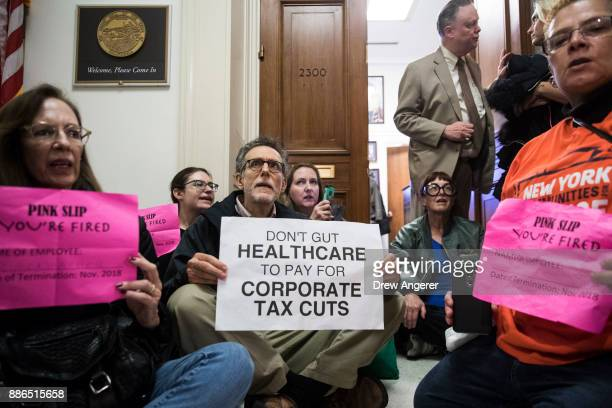 Activists stage a sitin to protest the GOP tax reform bill outside of office of Rep Dana Rohrabacher on Capitol Hill December 5 2017 in Washington DC...