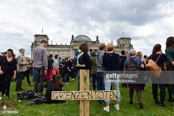 Activists stand around symbolic graves of immigrants and a wooden cross reading 'Borders Kill' in front of the Reichtsag building housing the...