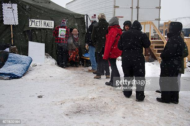 Activists stand in line for breakfast at the mess hall as it snows at Oceti Sakowin camp on the edge of the Standing Rock Sioux Reservation on...