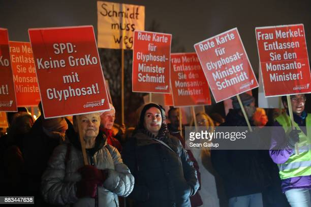 Activists standing outside Schloss Bellevue presidential palace where members of leading political parties were meeting inside protest against a...