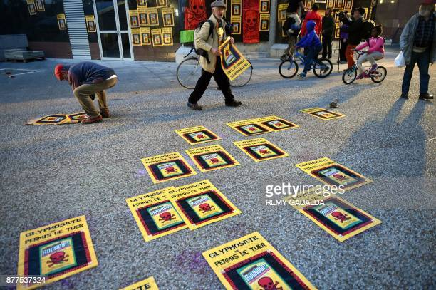 Activists stick posters on a walkway as they stage a demonstration against the use of pesticides such as Glyphosate in agriculture outside The Pierre...