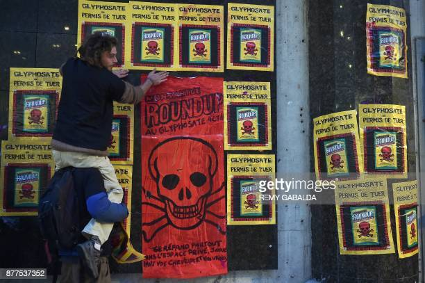 Activists stick posters on a wall as they stage a demonstration against the use of pesticides such as Glyphosate in agriculture outside The Pierre...