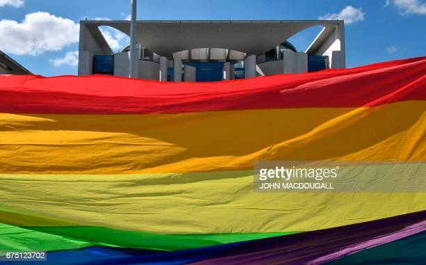 Activists stretch a giant rainbow banner in front of the Chancellery in Berlin on April 30 during a demonstration calling on Russian President to put...