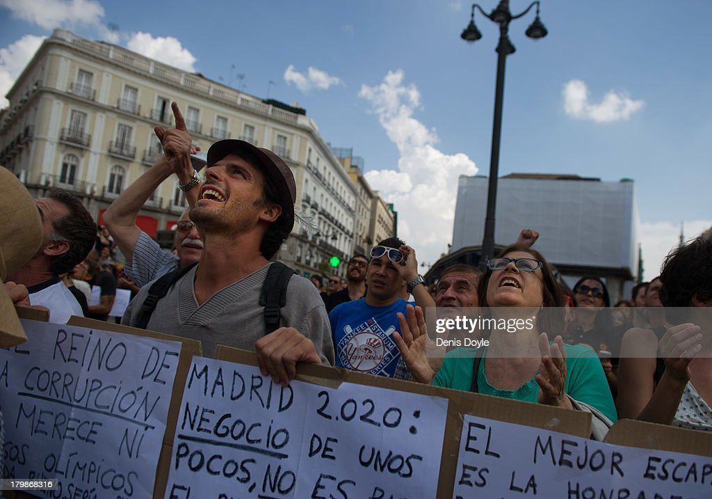 Activists support a man who hung from a lampost as a protest against the Madrid 2020 Olympic Candidacy and Madrid County Council policy over evictions at Puerta del Sol on September 7, 2013 in Madrid, Spain.