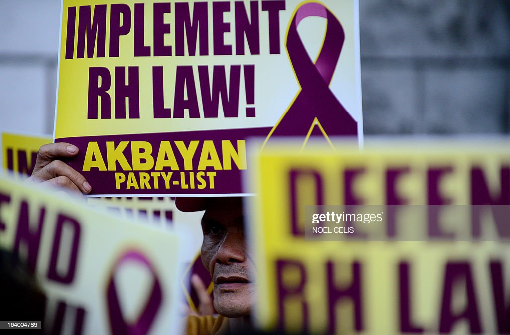 Activists supporting the Reproductive Health (RH) Law hold a protest in front of the Supreme Court building in Manila on March 19, 2013. The Philippines' highest court suspended a controversial birth control law that had met fierce opposition from the powerful Catholic Church. Voting 10-5, the Supreme Court issued a four-month freeze against the law, which requires government health centres to hand out free condoms and schools to teach sex education, court spokesman Theodore Te said. AFP PHOTO / Noel CELIS