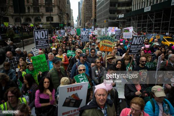 Activists take part in a Tax Day protest on April 15 2017 in New York City Thousands of activists march to Trump Tower to demand that President...