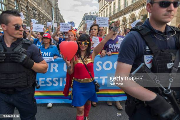Activists walk beside a security official while taking part in the Gay Pride parade in Paris on June 24 2017 2017 marks the 40th anniversary of the...