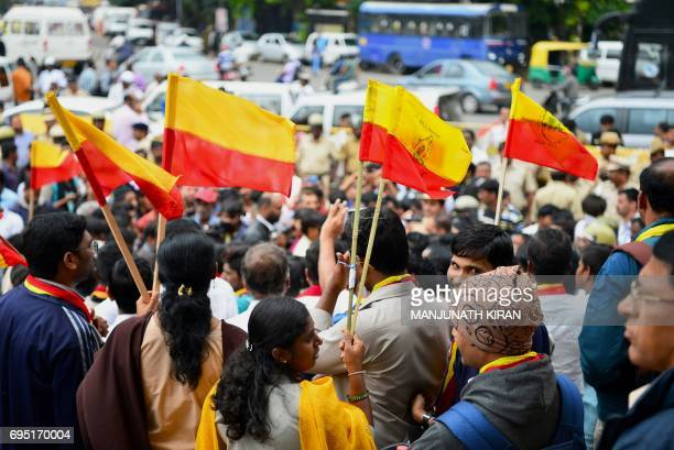 Activists wave Karnataka state flags during a protest in Bangalore on June 12 2017 ProKannada activists protested to urge government intervention in...