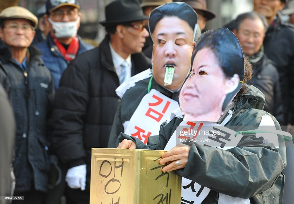 activists wear the face masks of North Korean leader Kim Jong-Un and his wife Ri Sol-Ju (R) as they 'beg' for money during an anti-Pyongyang rally urging North Korea to abandon nuclear weapons in Seoul on January 31. South Korean President Lee Myung-Bak held an emergency security meeting on January 31 that warned North Korea of 'serious consequences' if it went through with an expected nuclear test.