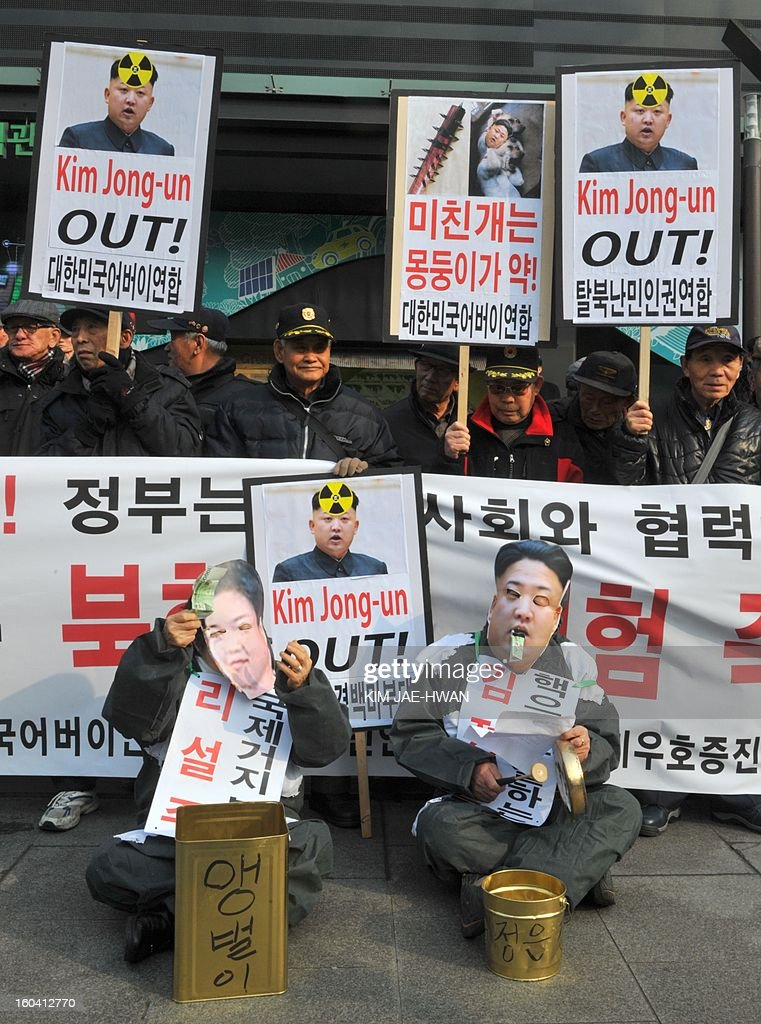 activists wear the face masks of North Korean leader Kim Jong-Un and his wife Ri Sol-Ju (bottom L) as they 'beg' for money during an anti-Pyongyang rally urging North Korea to abandon nuclear weapons in Seoul on January 31. South Korean President Lee Myung-Bak held an emergency security meeting on January 31 that warned North Korea of 'serious consequences' if it went through with an expected nuclear test.