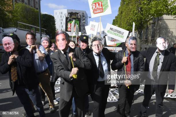 Activists wearing masks of candidates for the French election French presidential election candidate for the Solidarite et Progres party Jacques...
