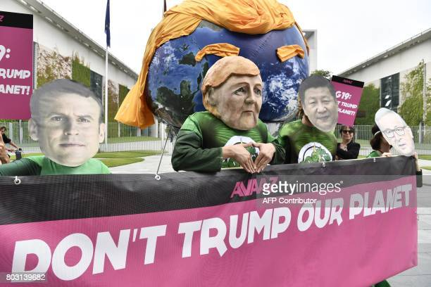 Activists wearing masks of French President Emmanuel Macron German Chancellor Angela Merkel China's President Xi Jinping and President of the...