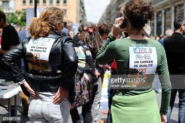 Activists wearing posters that read 'Ne fumez pas ne buvez pas ne mangez pas gras nous seuls sommes habilités à vous fournir un cancer de qualité'...
