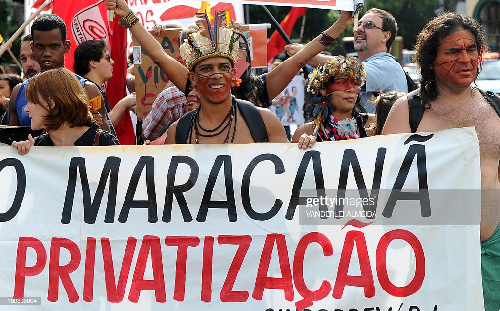 Activists --with some Brazilian natives among them-- protest in front of the Guanabara state government's palace against the privatization of the Mario Filho 'Maracana' stadium in Rio de Janeiro, Brazil, on April 11, 2013. Bidding for the privatization of Rio's iconic Maracana stadium was to go ahead as planned Thursday after a local court rejected an appeal to block the process. Maracana, which was built for the 1950 World Cup, is undergoing extensive renovation at a cost of 430 million dollars to host four Confederations Cup matches in June as well as seven World Cup games next year, including the finals of both tournaments. AFP PHOTO /VANDERLEI ALMEIDA