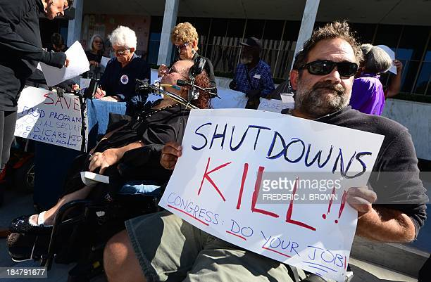 Activists with the California Alliance for Retired Americans hold placards while gathered for a diein to protest the government shutdown and possible...