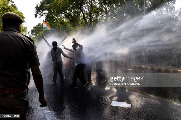 Activists with the Indian Youth Congress are hit with a water cannon fired by police during a protest following the completion of three years of...