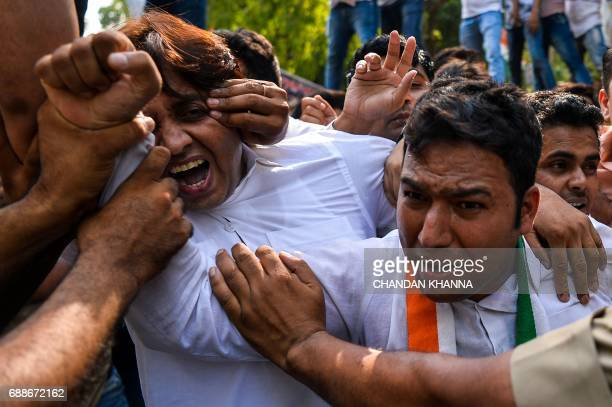 Activists with the Indian Youth Congress shout antigovernment slogans during a protest following the completion of three years of National Democratic...