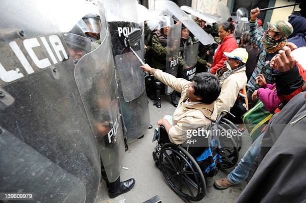 Activiststs taking part in a protest of impaired people struggle with riot police as they try to get to the Plaza de Armas square in La Paz on...