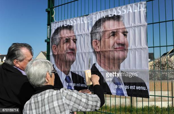 Activits glue campaign posters of French presidential Jean Lassalle few days ahead of the vote's first round on April 18 2017 in Le Guilvinec western...