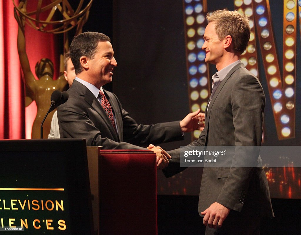 Acto Neil Patrick Harris (R) walks onstage to join Academy of Television Arts & Sciences Chairman & CEO Bruce Rosenblum (L) during the 65th Primetime Emmy Awards nominations at the Television Academy's Leonard H. Goldenson Theatre on July 18, 2013 in North Hollywood, California.