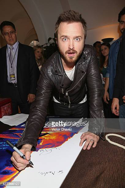Actor Aaron Paul signs a poster during a press junket and photocall to promote his new film 'Need For Speed' at Four Seasons Hotel on March 8 2014 in...