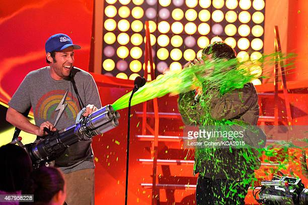 Actor Adam Sandler slimes actor Josh Gad onstage during Nickelodeon's 28th Annual Kids' Choice Awards held at The Forum on March 28 2015 in Inglewood...