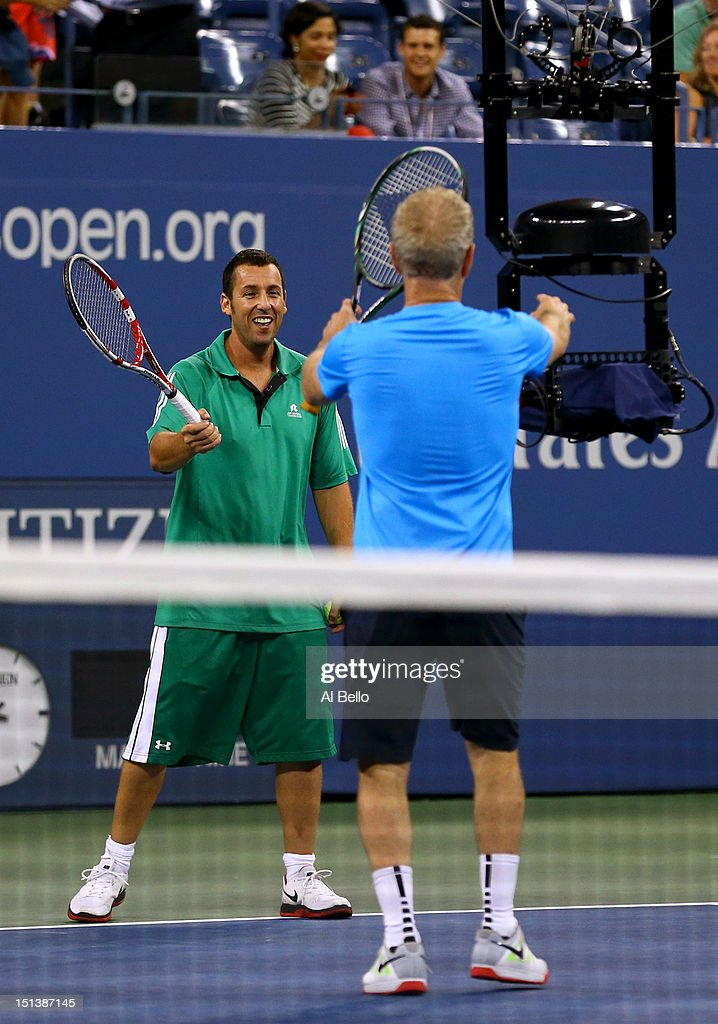 Actor Adam Sandler smiles as former tennis player John McEnroe grabs the spidercam during a celebrity doubles match on Day Eleven of the 2012 US Open...