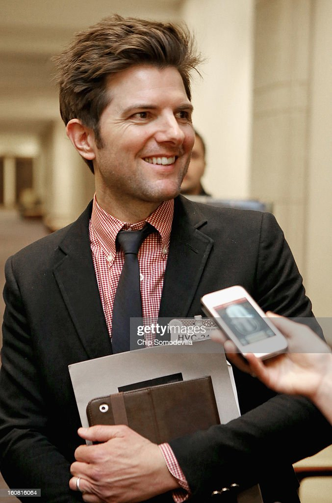 Actor Adam Scott talks with journalists after participating in a news conference hosted by the Mayors Against Illegal Guns and the Law Center to Prevent Gun Violence at the U.S. Capitol February 6, 2013 in Washington, DC. The artists, activists and politicians called for manditory background check on all gun purchases among other restrictions.