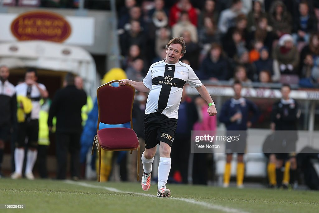Actor Adam Woodyatt carries a chair to the middle of the pitch during the William Hill Foundation Cup Celebrity Charity Challenge Match at Sixfields on December 9, 2012 in Northampton, England.