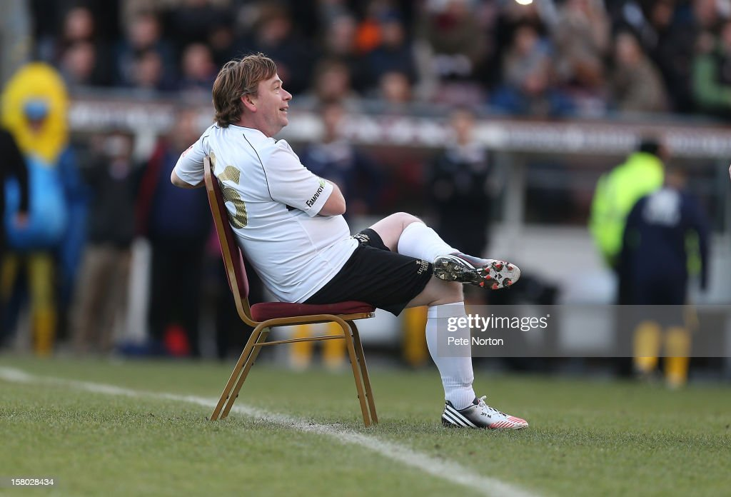 Actor Adam Woodyatt sits on a chair in the middle of the pitch during the William Hill Foundation Cup Celebrity Charity Challenge Match at Sixfields on December 9, 2012 in Northampton, England.