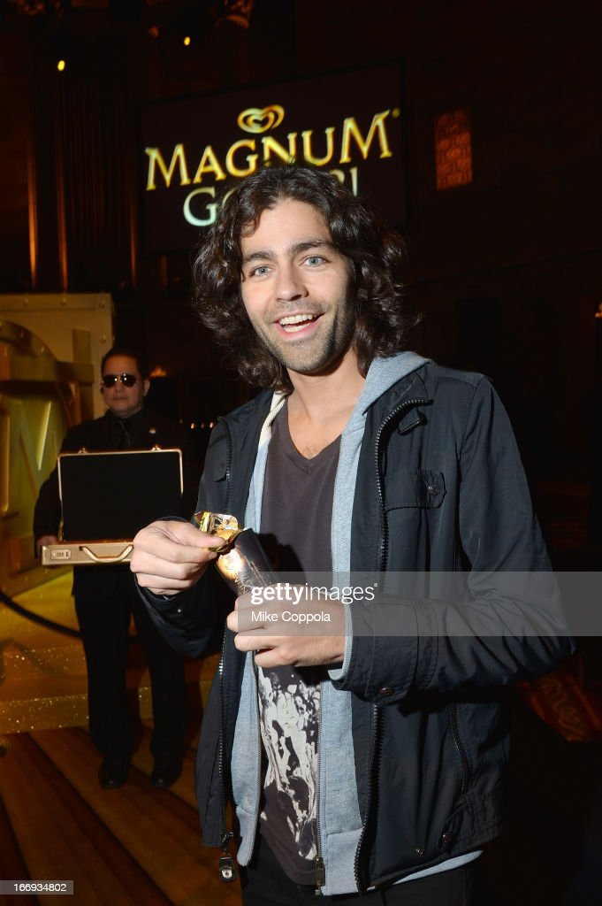 Actor <a gi-track='captionPersonalityLinkClicked' href=/galleries/search?phrase=Adrian+Grenier&family=editorial&specificpeople=211413 ng-click='$event.stopPropagation()'>Adrian Grenier</a> unwraps a MAGNUM Gold?! bar at the 'As Good As Gold' MAGNUM Gold?! Film Premiere on April 18, 2013 in New York City.