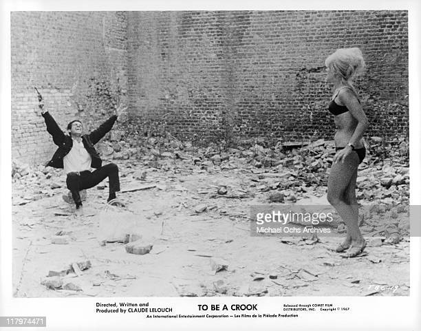 Actor aims gun to sky while actress watches in a scene from the film 'To Be A Crook' aka 'Une fille et des fusils' 1967