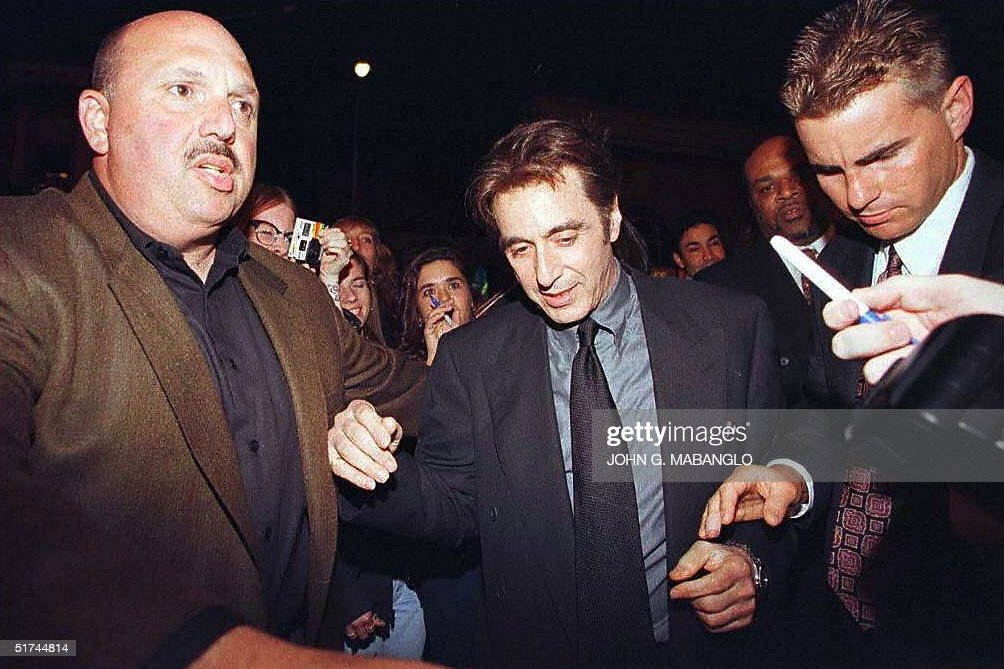 US actor Al Pacino is quickly escorted inside the theatre after being bombarded by fans during the 25th Annivesary presentation of the Godfather in...