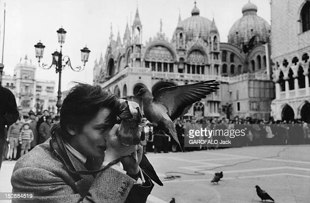 Actor Alain Delon takes photographs on the Place SaintMarc during the test for the filming of the movie 'Marco Polo' on March 12 1962 in Venice Italy