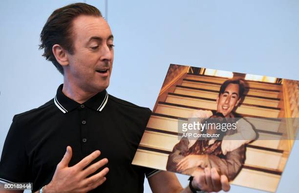 Actor Alan Cumming speaks while holding a photograph of himself with Tonka his chimpanzee costar from the 1997 film 'Buddy' during an announcement on...