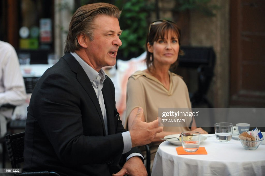 US actor Alec Baldwin and US actress and model Carol Alt sit on the set at a terrace at Piazza della Pace in central Rome during the filming of US...