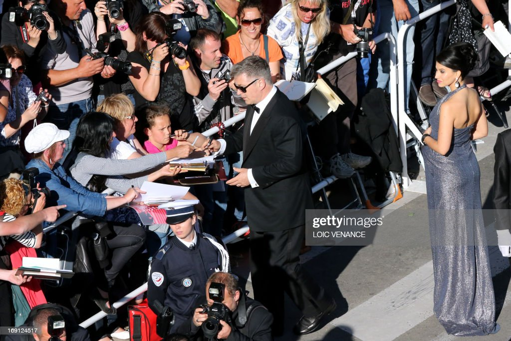 US actor Alec Baldwin (C) signs autographs on May 20, 2013 as he arrives with his wife Hilaria Thomas for the screening of the film 'Blood Ties' presented Out of Competition at the 66th edition of the Cannes Film Festival in Cannes. Cannes, one of the world's top film festivals, opened on May 15 and will climax on May 26 with awards selected by a jury headed this year by Hollywood legend Steven Spielberg.