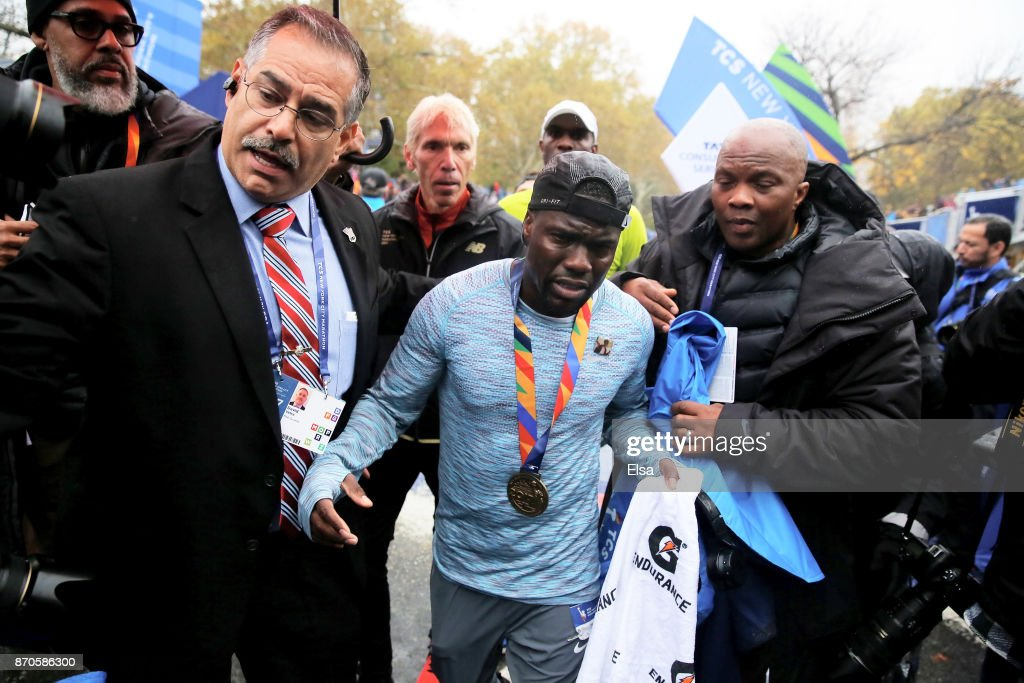 Actor and comedian Kevin Hart is helped as he crosses the finish line during the TCS New York City Marathon in Central Park on November 5, 2017 in New York City.