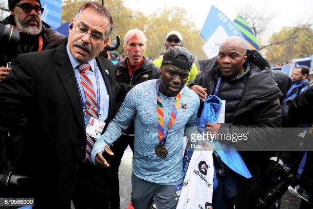 Actor and comedian Kevin Hart is helped as he crosses the finish line during the TCS New York City Marathon in Central Park on November 5 2017 in New...