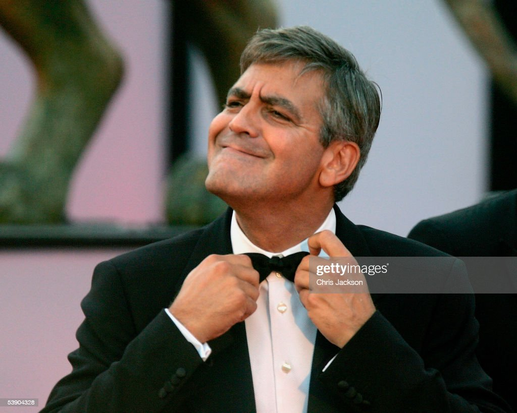 Actor and Director George Clooney plays with his bowtie at the premiere for 'Good Night, And Good Luck' at the Palazzo del Cinema as part of the 62nd Venice Film Festival on September 1, 2005 in Venice, Italy.