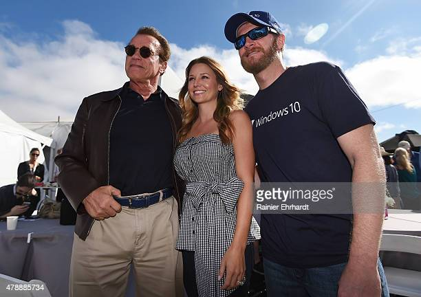 Actor and former governor of California Arnold Schwarzenegger Amy Reimann and Dale Earnhardt Jr driver of the Microsoft Chevrolet pose for a picture...