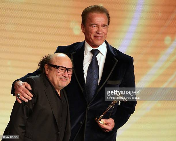US actor and former governor of California Arnold Schwarzenegger poses after receiving from US actor Danny DeVito his lifetime achievement award at...
