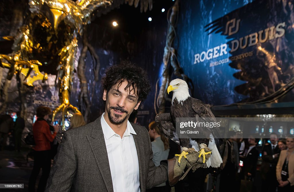 Actor and friend of the Roger Dubuis brand, Tomer Sisley holds an eagle as he visits the booth during the 23rd Salon International de la Haute Horlogerie at the Geneva Palexpo on January 23, 2013 in Geneva, Switzerland.