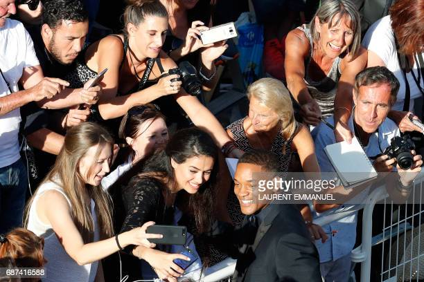 US actor and member of the Feature Film jury Will Smith poses for selfies with fans as he arrives on May 23 2017 for the '70th Anniversary' ceremony...