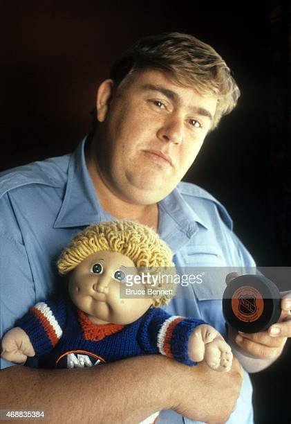 Actor and New York Islanders fan John Candy poses with a puck and holds a Cabbage Patch doll during a photo shoot in August 1985 in Uniondale New York
