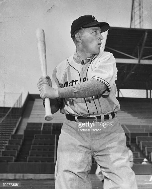 Actor and singer Bing Crosby wearing a baseball uniform and holding his bat aloft on a baseball field circa 1945