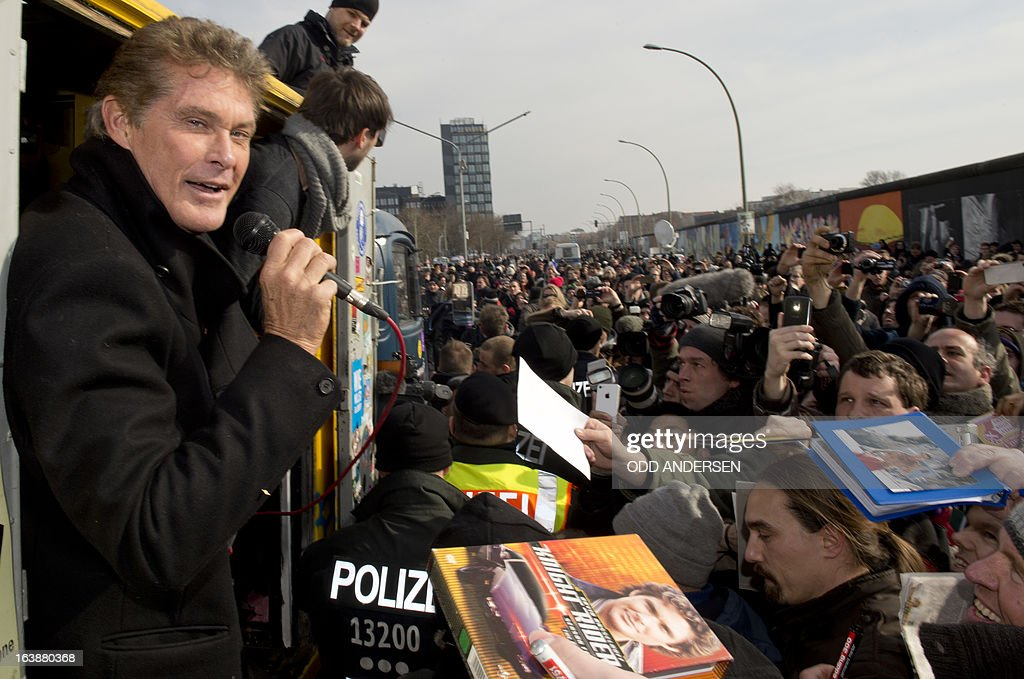 US actor and singer David Hasselhoff gestures as people ask for an autograph while he talks from a truck at the East Side Gallery on March 17, 2013 in Berlin, Germany to protest the planned demolition of a part of these remains of the former Berlin Wall.Thousands of people gathered as the former Bay watch star came to the German capital to lend his support to the movement that wants to preserve the 1,3km long stretch of the cold war symbol and keep the land along river Spree as public land. AFP PHOTO / ODD ANDERSEN