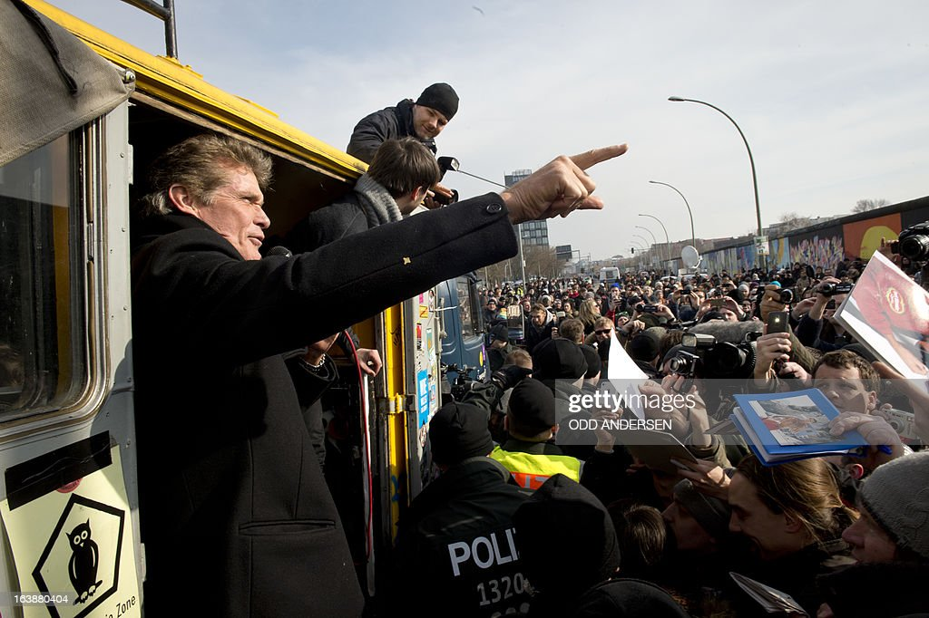 US actor and singer David Hasselhoff gestures as people ask for an autograph while he talks from a truck at the East Side Gallery in Berlin, Germany, on March 17, 2013 to protest the planned demolition of a part of these remains of the former Berlin Wall.Thousands of people gathered as the former Bay watch star came to the German capital to lend his support to the movement that wants to preserve the 1,3km long stretch of the cold war symbol and keep the land along river Spree as public land.