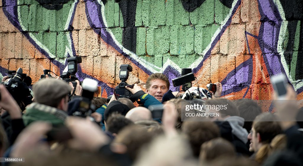 US actor and singer David Hasselhoff is mobbed by media and fans as he arrives for a walk along the Berlin Wall at the East Side Gallery on March 17, 2013 in Berlin, Germany to protest against the planned demolition of a part of these remains of the former Berlin Wall.Thousands of people gathered as the former Bay Watch star came to the German capital to lend his support to the movement that wants to preserve the 1,3km long stretch of the cold war symbol and keep the land along the river Spree as public land.