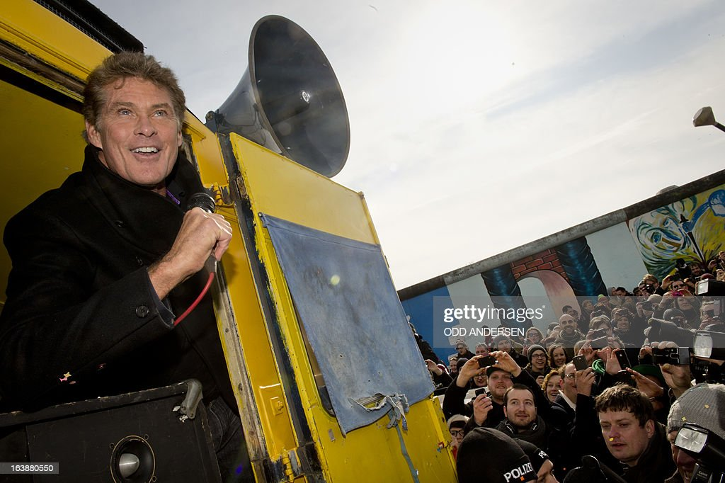 US actor and singer David Hasselhoff speaks to the crowd from a truck as he tours the East Side Gallery part of the remains of the former Wall in Berlin on March 17, 2013. Thousand of people turned out as the former Bay Watch star came to the German capital to lend his support to the movement for that want to preserve the 1,3km long stretch of the cold war symbol and keep the land along river Spree as public land.